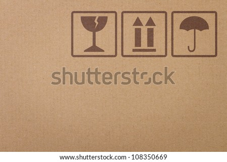 Safety, fragile icons on a cardboard parcel with copy space - stock photo
