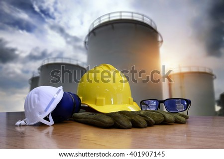 Safety gear kit standing in front of oil refinery background.