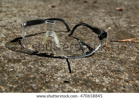 Safety goggles resting on rough concrete outside in daylight.