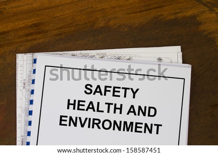 Safety health and environment manual with wood texture background. - stock photo