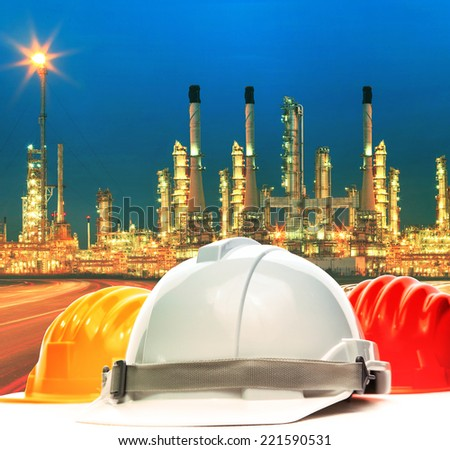 safety helmet against beautiful lighting of oil refinery plant in petrochemical industry estate use as industrial and safety topic background - stock photo