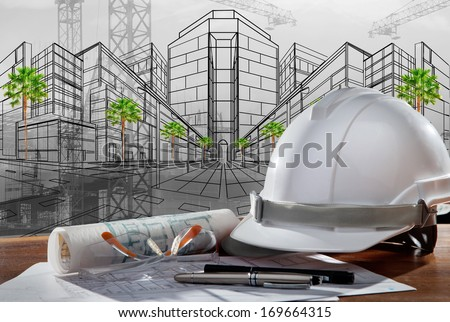 safety helmet and architect plan on wood table with sunset scene and building construction - stock photo