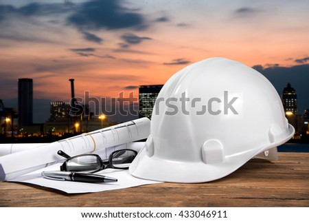safety helmet and architect plant on wood table with city sunset scene and building construction - stock photo