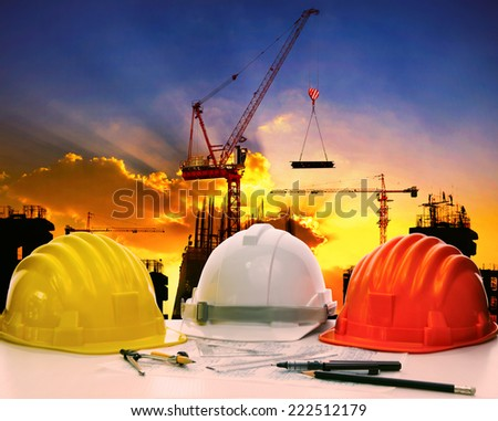 safety helmet on civil engineer working table against crane lifting material in building construction site  - stock photo