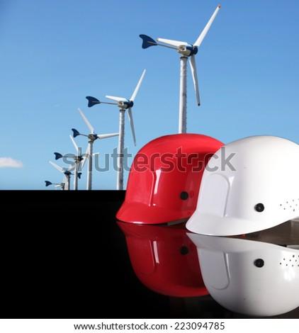 safety helmet on civil engineer working table against wind turbine site - stock photo