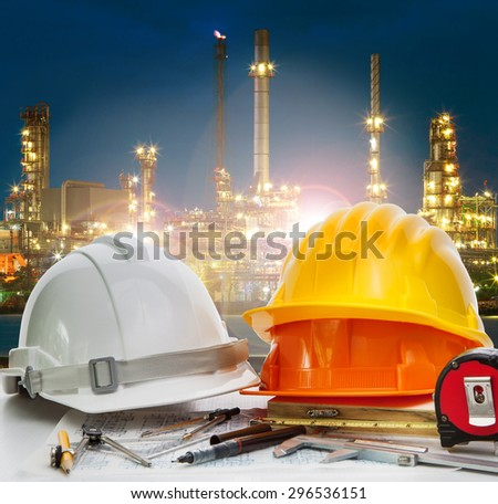 safety helmet on engineer working table against oil refinery plant