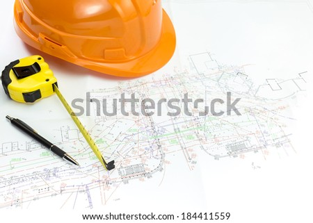 Safety helmet, pencil and tape measure over onstruction plans