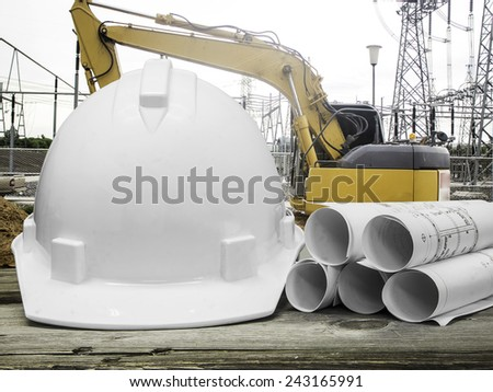 Safety helmet with architectural blueprint of office building over Construction site background - stock photo