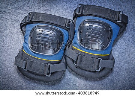 Safety knee protectors on black background construction concept. - stock photo