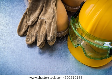 Safety leather boots protective gloves hard hat and transparent plastic glasses on scratched metallic background close up image construction concept. - stock photo