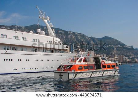 Safety lifeboat from cruise ship alongside big white yacht ship.  - stock photo