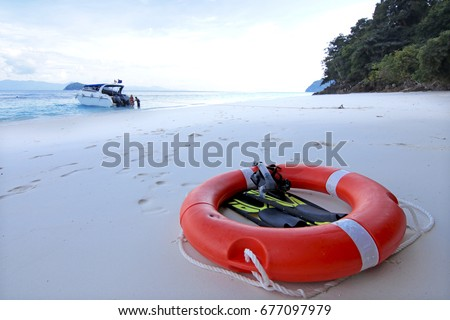 Safety lifebuoy and driving equipment on white sand beach.
