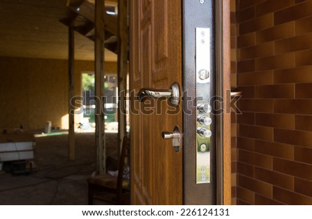 Safety lock on a new wooden front door showing the three security cylinders required by insurance companies for best premium quotations - stock photo