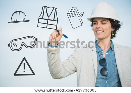 Safety manager. Successful independent engineer smiling woman with safety helmet drawing on the air glasses, vest, gloves. Pioneer leader woman at work. - stock photo