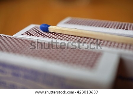 Safety match stick with a small blue head on the top of box of safety matches with its black striking surface with the honeycomb shapes on the narrower side  - stock photo