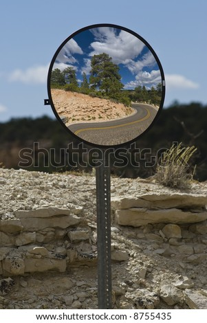 Safety mirror on hairpin turn on the road to Cape Royal on the North Rim of the Grand Canyon. - stock photo