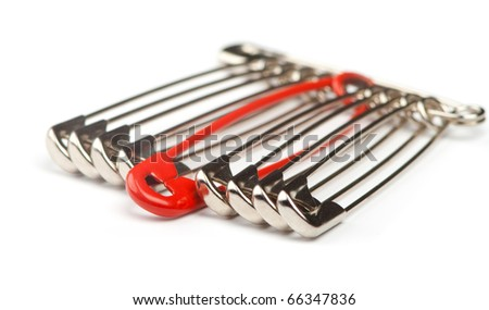 Safety pins in a row with one distinguishing red pin - stock photo