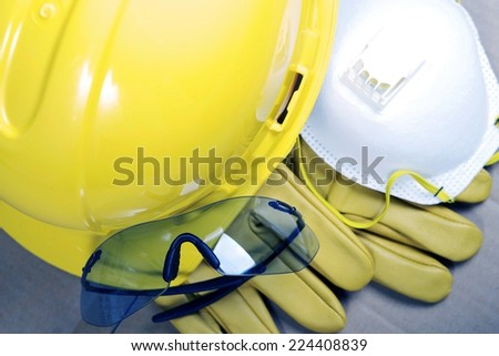 Safety Protective Work Equipment. Yellow Helmet, Glasses, Gloves and Mask. Protection Gear Closeup. - stock photo