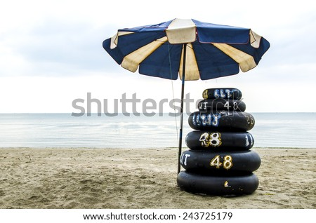 Safety ring on the beach with umbrella - stock photo
