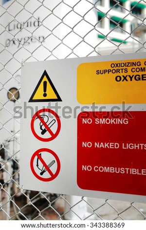Safety signs symbols ( DANGER-FLAMMABLE MATERIAL,NO SMOKING ) in front of the large Liquid Oxygen tank. - stock photo