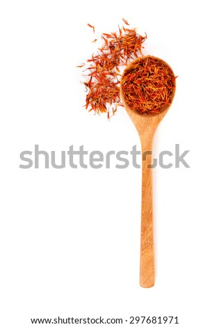 Safflower petals in a spoon on white background - stock photo