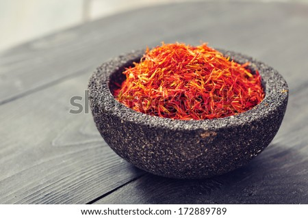 Saffron in stone bowl on wooden background. Small shallow DOF. - stock photo
