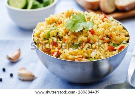 saffron rice with vegetables and cilantro on a blue background. the toning. selective focus  - stock photo