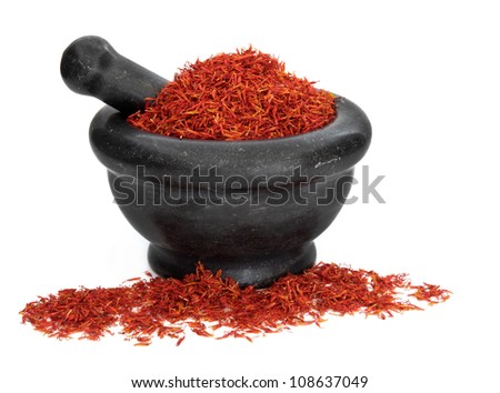 Saffron spice used in cooking and traditional chinese herbal medicine in a black marble mortar with pestle over white background. Hong hua - stock photo