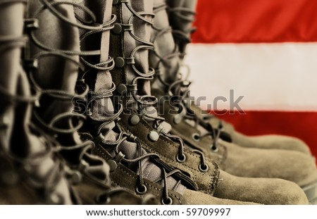 Sage green military combat boots with US flag in the background. - stock photo