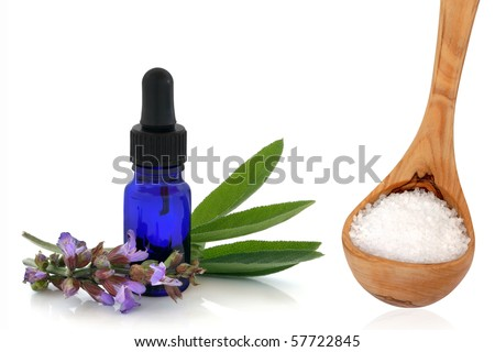 Sage herb leaf and flower sprigs and aromatherapy essential oil bottle, with sea salt in an olive wood ladle, isolated over white background. - stock photo
