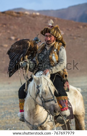 SAGSAY, MONGOLIA - SEP 28, 2017: Golden Eagle Hunter teaches her young daughter hunting with birds of prey to the hare in desert mountain of Western Mongolia.