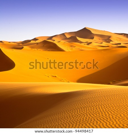 Sahara desert landscape with blue sky. Dunes background.
