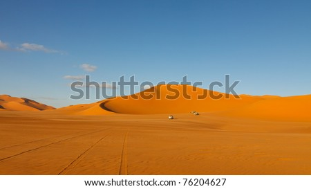 Sahara Desert Safari - Off-road vehicle driving in the Murzuq Desert, Sahara, Libya - stock photo