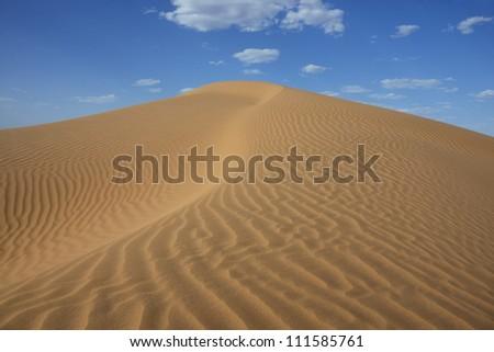 Sahara desert sand dune with cloudy blue sky at Erg Lihoudi, M'hamid, Morocco - stock photo