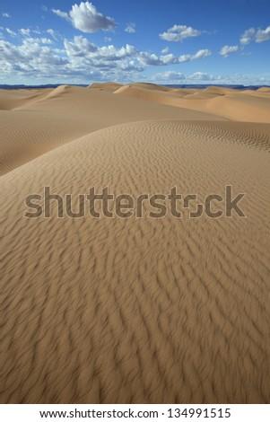 Sahara desert sand dunes with cloudy blue sky at Erg Lihoudi, M'hamid, Morocco - stock photo