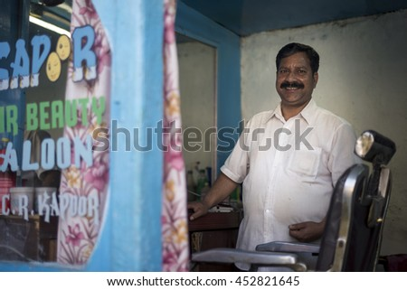 SAHARAN, INDIA - Jun 05, 2016: A barber stand beside antique barber chair with a friendly smile inside hair saloon.