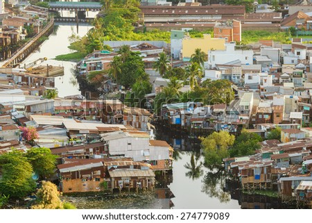 SAIGON, VIETNAM - NOVEMBER 16, 2014. Colorful squatter shacks and houses in a Slum Urban Area in the sunset at Ho Chi Minh City, Vietnam. Ho Chi Minh city (or Saigon) is the biggest city in Vietnam. - stock photo