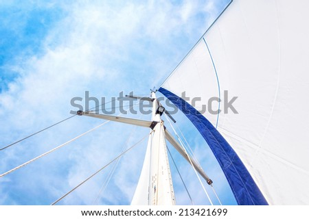 Sail and mast with sky in the background