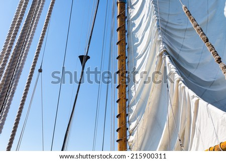 Sail and rigging being hoisted against a clear blue sky. Tall ship schooner under sail at sea. - stock photo