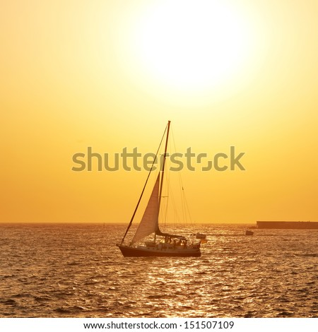 Sail boat against sea sunset. Colorful marine landscape.