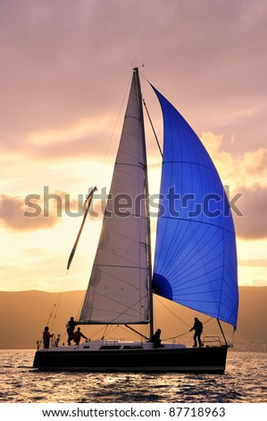Sail boat against sun with unrecognizable people - stock photo