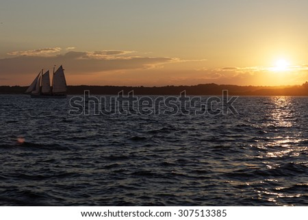 Sail boat at sunset on the ocean. - stock photo