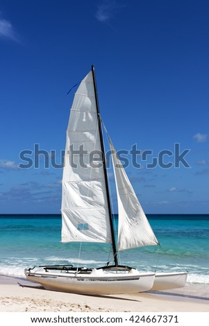 Sail boat, catamaran, on tropical beach with blue sky and water background