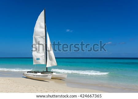 Sail boat, catamaran, on tropical beach with blue water background