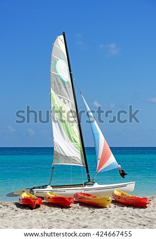 Sail boat, catamaran, with four canoes on tropical beach with blue sky and water background - stock photo