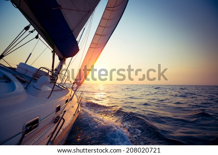Sail boat gliding in open sea at sunset - stock photo