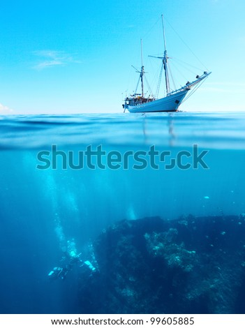 Sail boat in a tropical calm sea on a surface and divers underwater exploring a shipwreck - stock photo