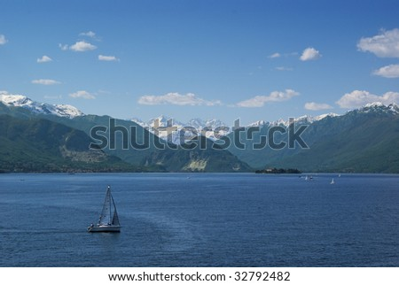 Sail boat in lake Maggiore (northern Italy) with snowy Alps at the horizon - stock photo