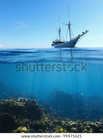 Sail boat in tropical calm sea and coral reef underwater - stock photo