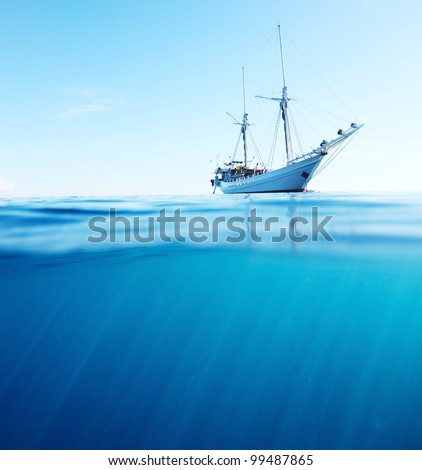 Sail boat in tropical calm sea on a surface and underwater sea view with sun beams - stock photo